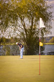 Senior golfer putting on green. stock photos