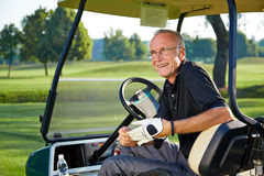 Senior golfer sitting in a golfcart and smile. Senior man sitting in a golfcart on the green Stock Photo
