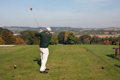 Senior golfer teeing off in autumn. A senior golfer teeing off with a driver from an elevated tee in early autumn. Yellow ball, with tee shot heading straight stock photography