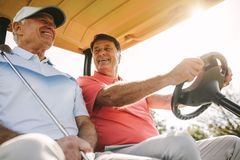 Senior golfers in a cart after round of golf on sunny day. Low angle shot of two senior men driving in a golf cart. Two male golfers in a cart enjoying a round stock photography
