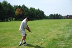 Senior Golfing. A senior golfer takes his second shot from the edge of the fairway Stock Photo