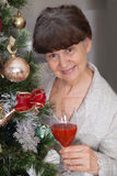 Senior good looking woman against of Christmas tree. Christmas background Stock Photo