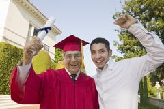 Senior Graduate hoisting diploma with son Royalty Free Stock Photography