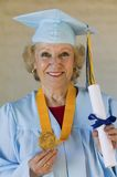 Senior graduate holding diploma and medal Royalty Free Stock Image