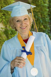 Senior Graduate Holding Diploma Outside Stock Photo