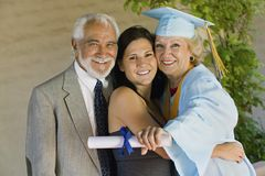 Senior graduate hugging granddaughter with husband Royalty Free Stock Photo