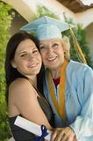 Senior graduate hugging granddaughter outside Stock Images
