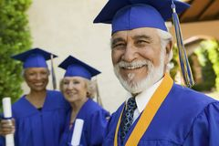 Senior graduate smiling outside with others behind Royalty Free Stock Images