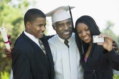 Senior graduate taking picture with grandchildren outside Stock Photos