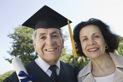 Senior graduate and wife outside Royalty Free Stock Image