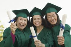 Senior Graduates hoisting diplomas Stock Photo