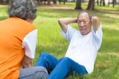 Senior grandfather doing sit-ups in the park Stock Photos