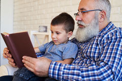 A senior grandfather and his grandson reading attentively an int Stock Photography
