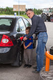 Senior grandfather with young boy refilling car Royalty Free Stock Image