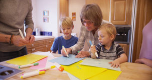 Senior grandma teaching grandchildren to draw Stock Images