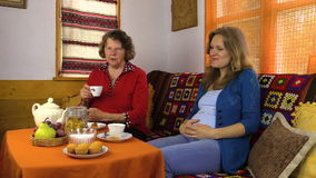 Senior grandma woman and young pregnant granddaughter have talk stock footage