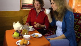 Senior grandma and young granddaughter eat sweets with tea stock video footage
