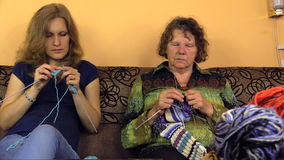 Senior grandma and young granddaughter talk and knit stock video footage
