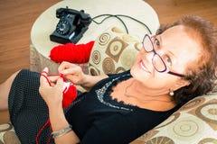 Senior Grandmother sitting enjoying her knitting Stock Photography