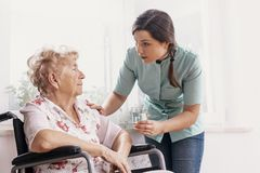 Senior on wheelchair, supporting nurse giving her glass of water stock photos
