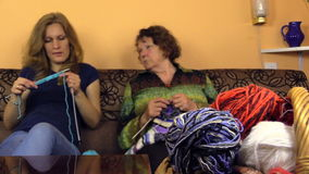 Senior grandmother and young granddaughter talk and knit Stock Image