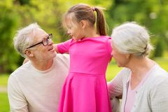 Senior grandparents and granddaughter at park. Family, generation and people concept - happy smiling grandmother, grandfather and little granddaughter at park Royalty Free Stock Photo