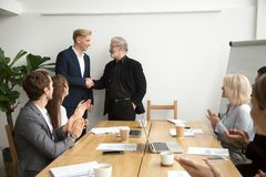 Senior boss promoting employee shaking hands team applauding at. Senior gray-haired businessman boss promoting male employee thanking appreciating good work Royalty Free Stock Photography