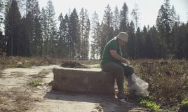 Senior green activist sorts garbage. Collected in the forest. Save nature concept stock photo