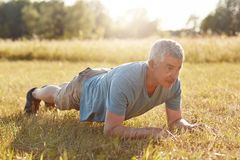 Senior grey haired male has athletic and fitness training outside, makes push ups, looks into distance, enjoys nice weather and be. Autiful nature for workout Stock Images