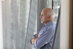 Senior grey-haired man standing deep in thought. In front of a window with folded arms and a deadpan serious expression, close up in profile indoors royalty free stock photos
