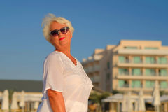 Senior grey haired woman staying near building. Attractive senior grey haired woman staying near building.a woman dressed in a white blouse decorated with three Stock Photo