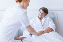 Senior grey woman lying in white hospital bed with young helpful nurse holding her hand royalty free stock photography