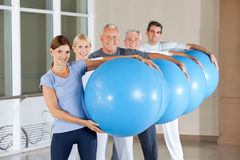 Senior group carrying gym balls Royalty Free Stock Images