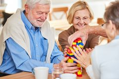 Senior group with dementia stacks building blocks. Senior group with dementia stacks together colorful building blocks in retirement home royalty free stock images