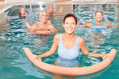 Senior group does water aerobics. Senior group doing water aerobics in pool with young physiotherapist royalty free stock photo