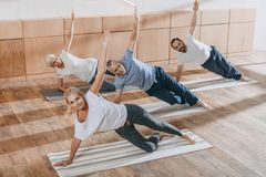 Senior group of people with instructor exercising on yoga mats. In fitness studio stock photography