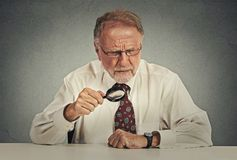 Senior grumpy businessman looking through magnifying glass Stock Image