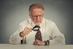 Senior grumpy businessman looking through magnifying glass stock image