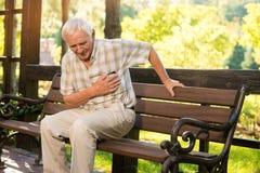 Senior guy has heartache. Elderly man on park bench. Too much stress. Chronic disease of heart Royalty Free Stock Photo