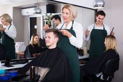 Senior hairdresser serving teenager Royalty Free Stock Photo