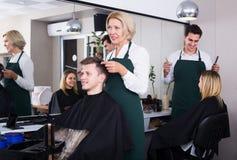 Senior hairdresser serving teenager. Positive senior women hairdresser serving teenager in chair Stock Images