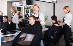 Senior hairdresser serving teenager Stock Photography
