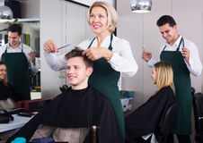 Senior hairdresser serving teenager Stock Photo