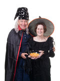 Senior Halloween couple handing out candy. A senior couple having fun on Halloween handing out candy corn to the trick or treater Stock Photo