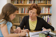 Senior halping child doing homework Stock Photo