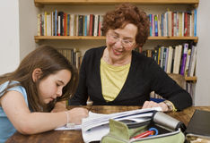 Senior halping child doing homework Royalty Free Stock Photos