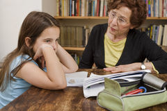 Senior halping child doing homework Royalty Free Stock Images