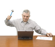 Senior with hammer and laptop Stock Photos