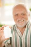 Senior hand in focus holding medicine phial Stock Images