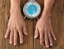 Senior hand and old clock on wood table Royalty Free Stock Image